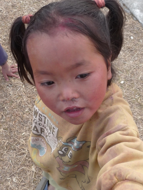 Snotty-nosed, but carefree, Nepali girl